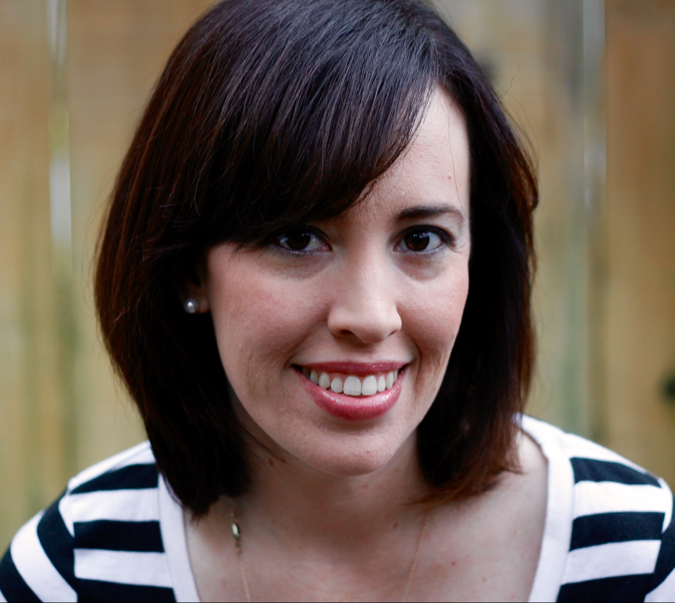 Headshot of author Jennifer Torres, wearing a black and white striped shirt and sitting in front of wood fence.